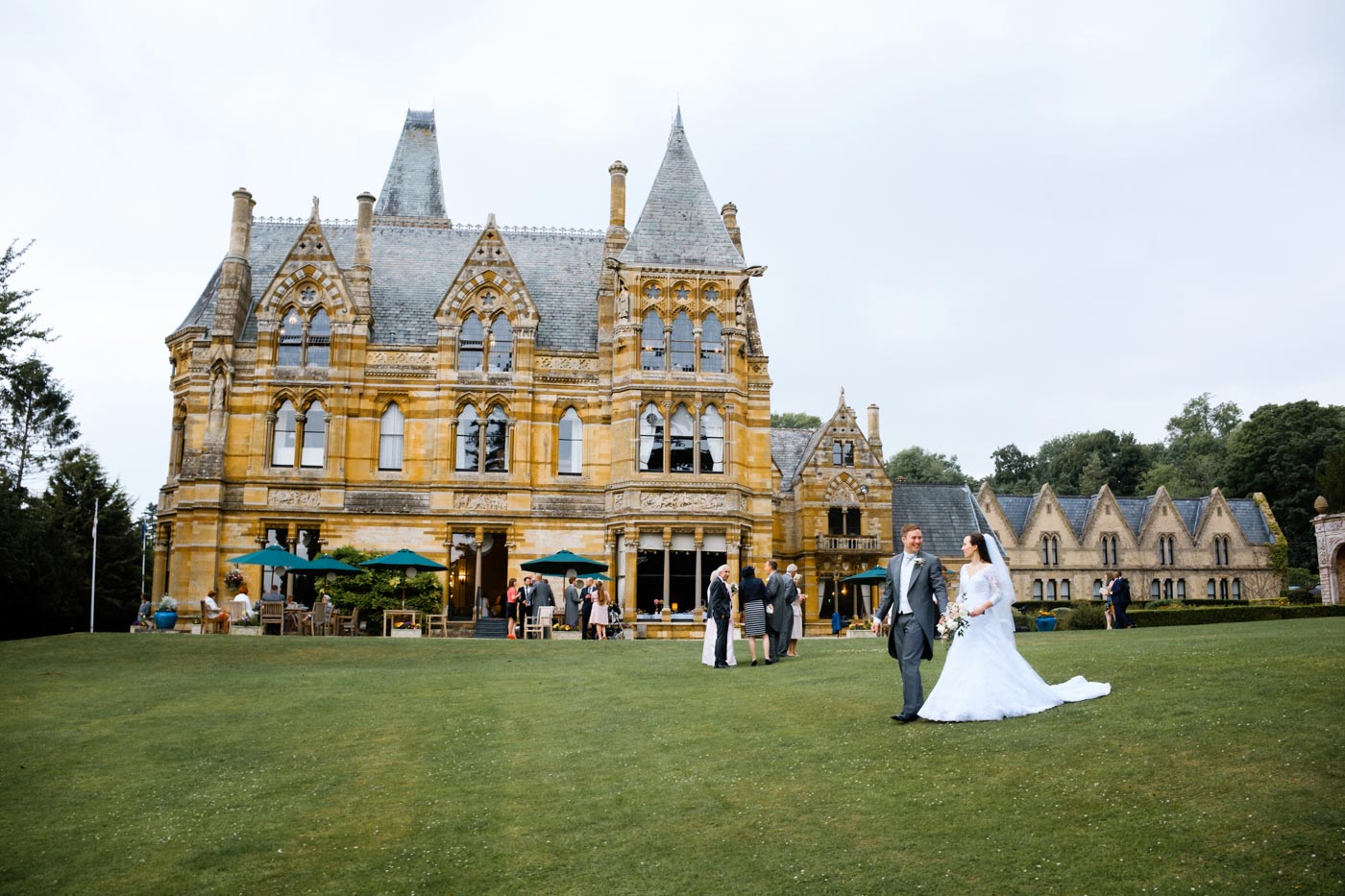 Groom and bride walking in the gorounds of Ettington Park Hotel