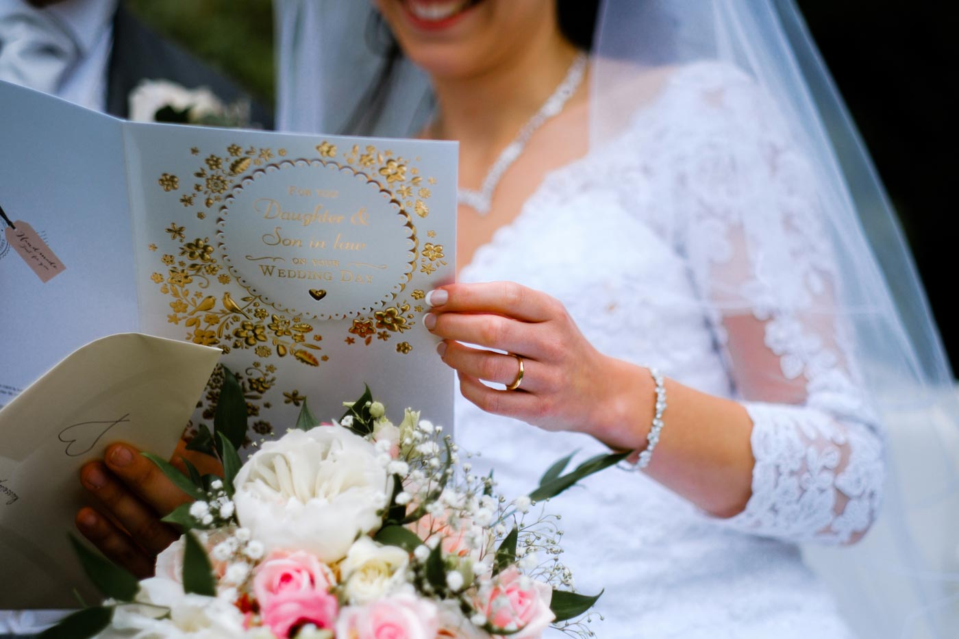 Bride and groom reading card from Bride's parents to them both