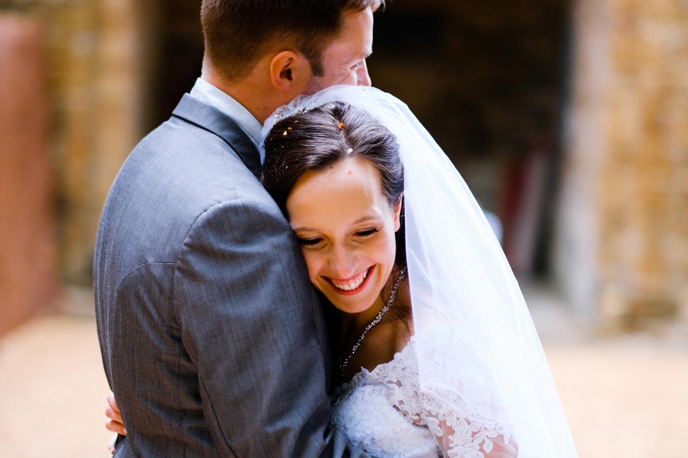 Bride being hugged by her groom