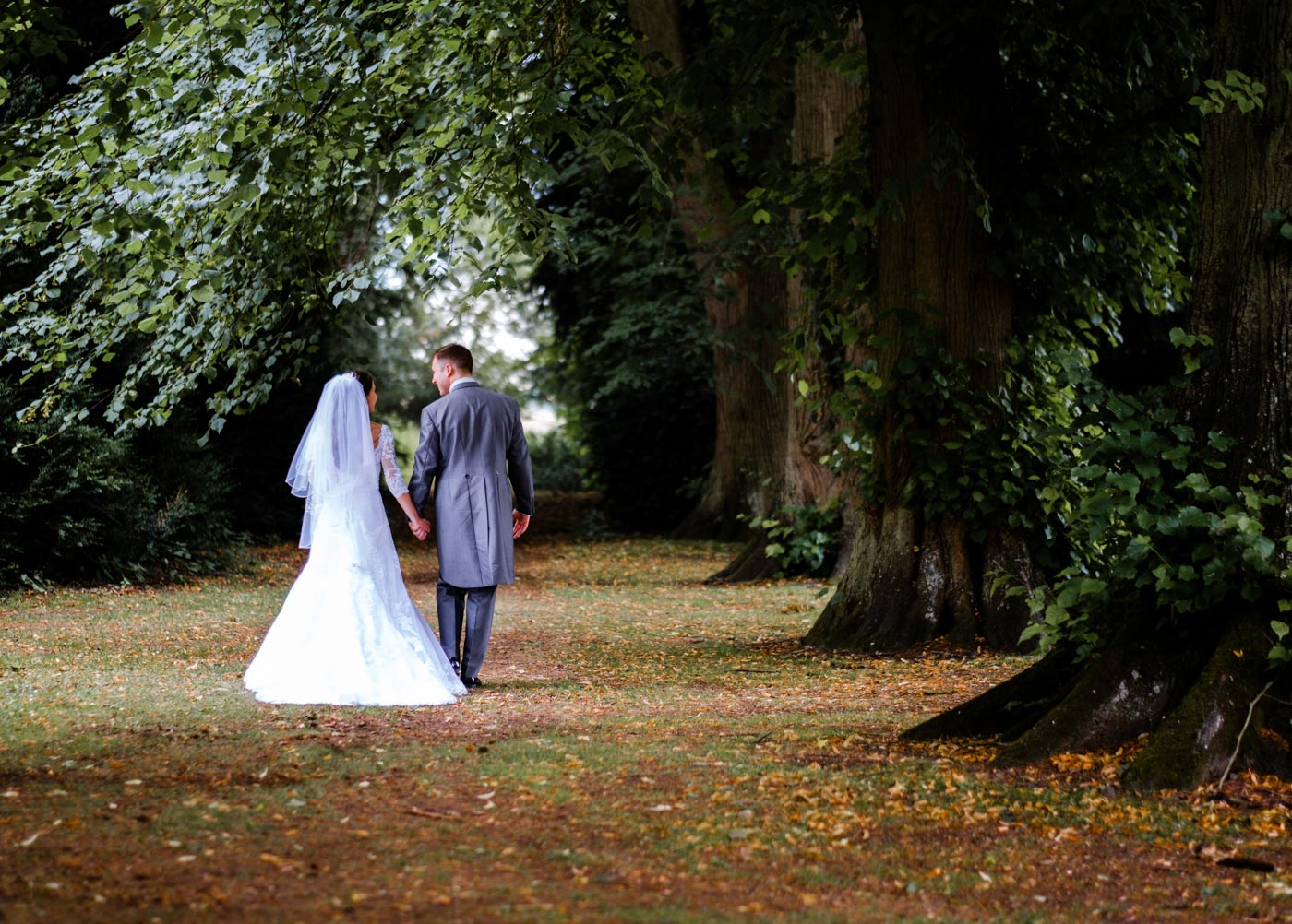 Bride and groom walking in the grounds after their Ettington Park Hotel wedding