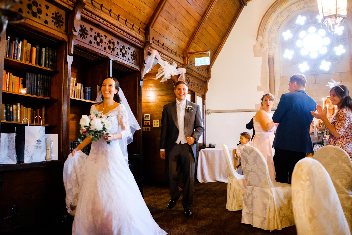 Bride and groom enters the Long Gallery room at Ettington Park Hotel
