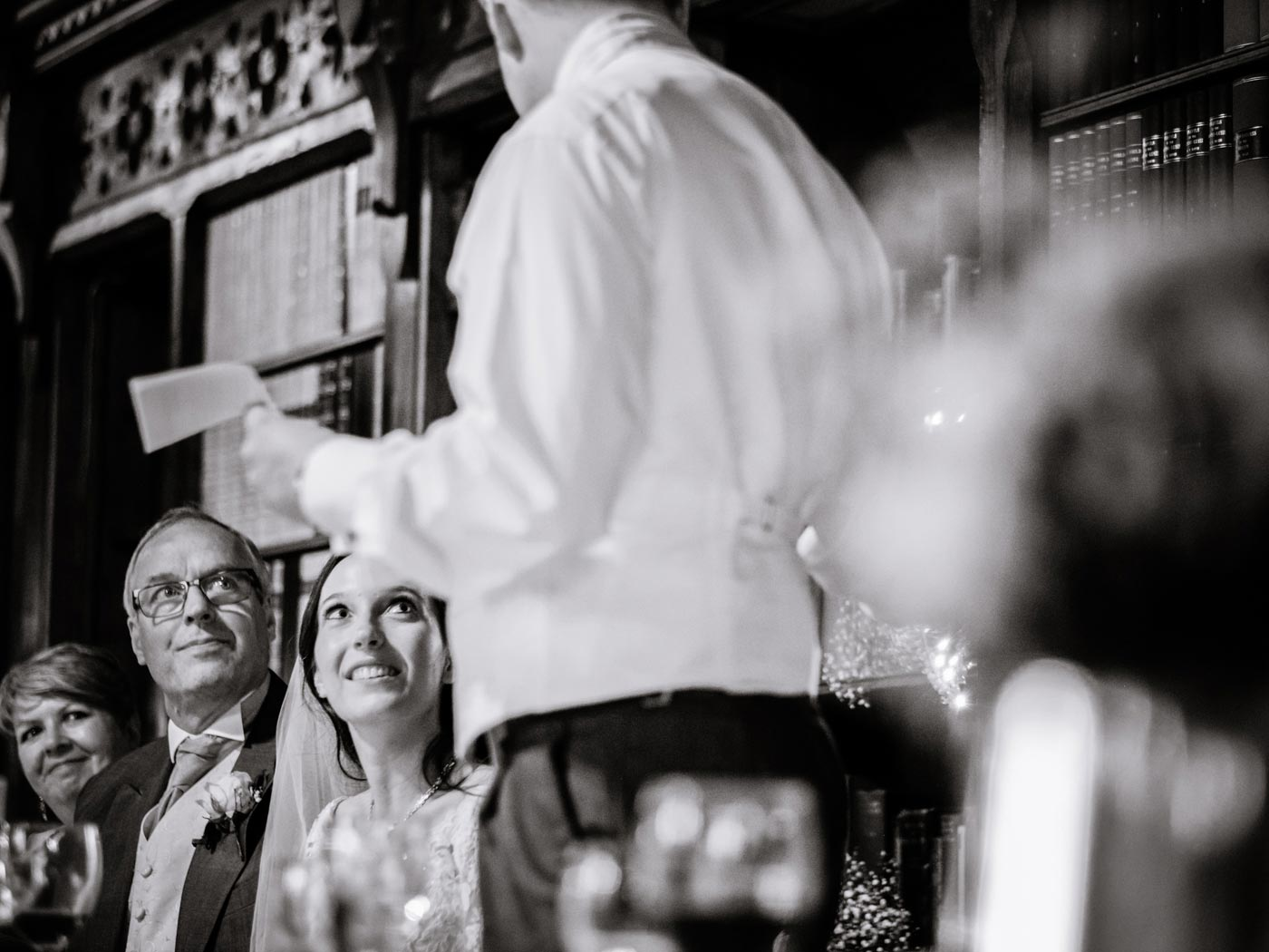 Bride, father and mother watching groom during his speech