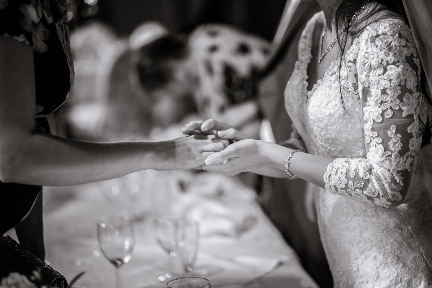 Bride tenderly holding the hand of a guest at Ettington Park Hotel