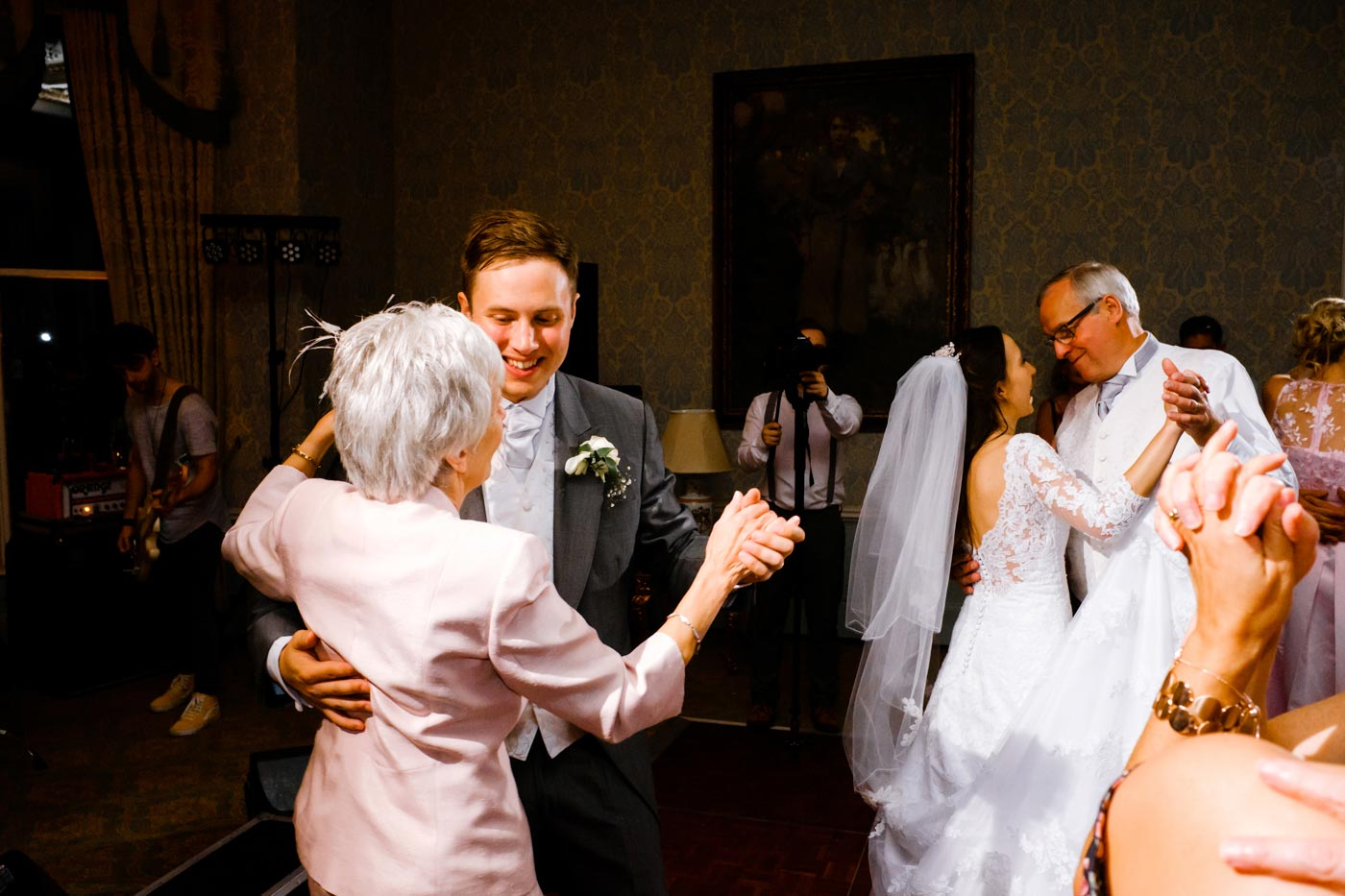 Groom dancing with his mother while bride dances with her father in the background at Ettington Park Hotel