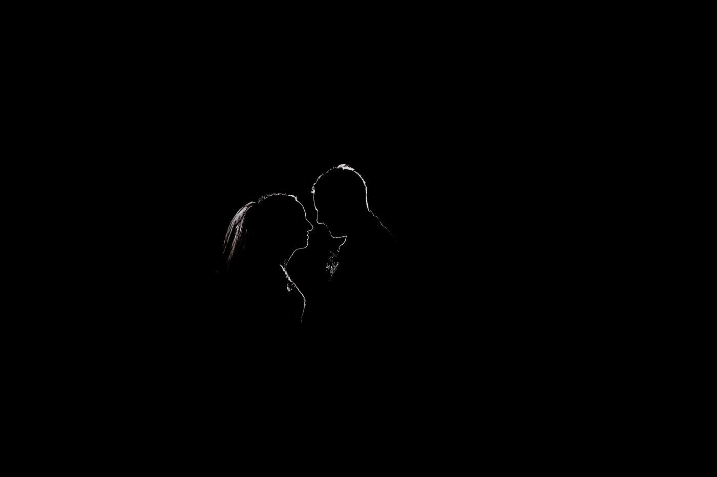 Silhouette of bride and groom by Clive Blair Photography