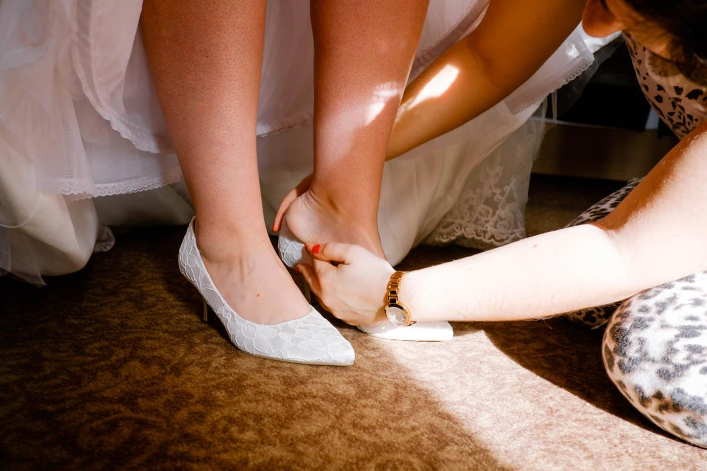 Bride having her shoes put on for her
