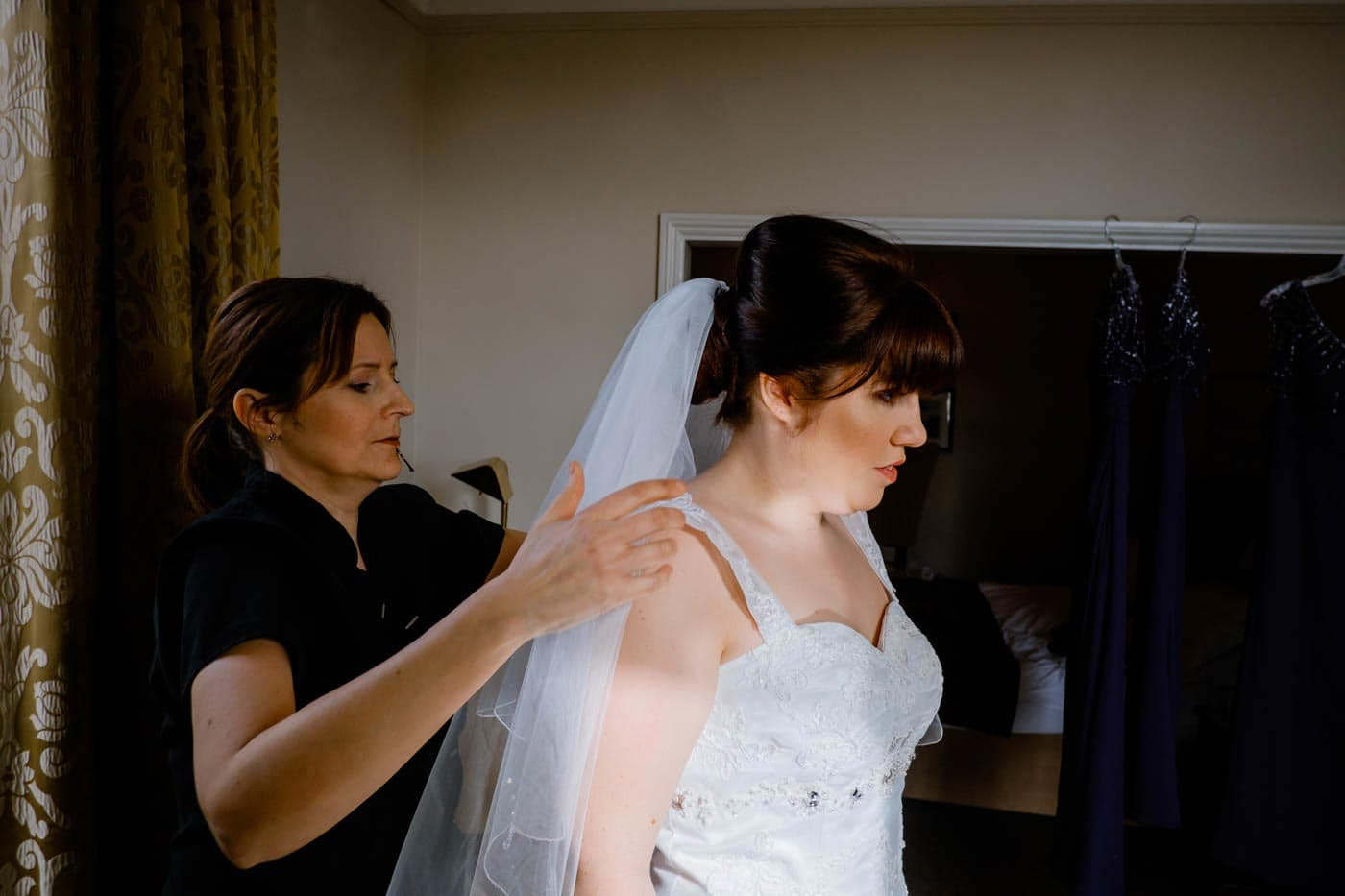 Bride having finishing touched to her veil