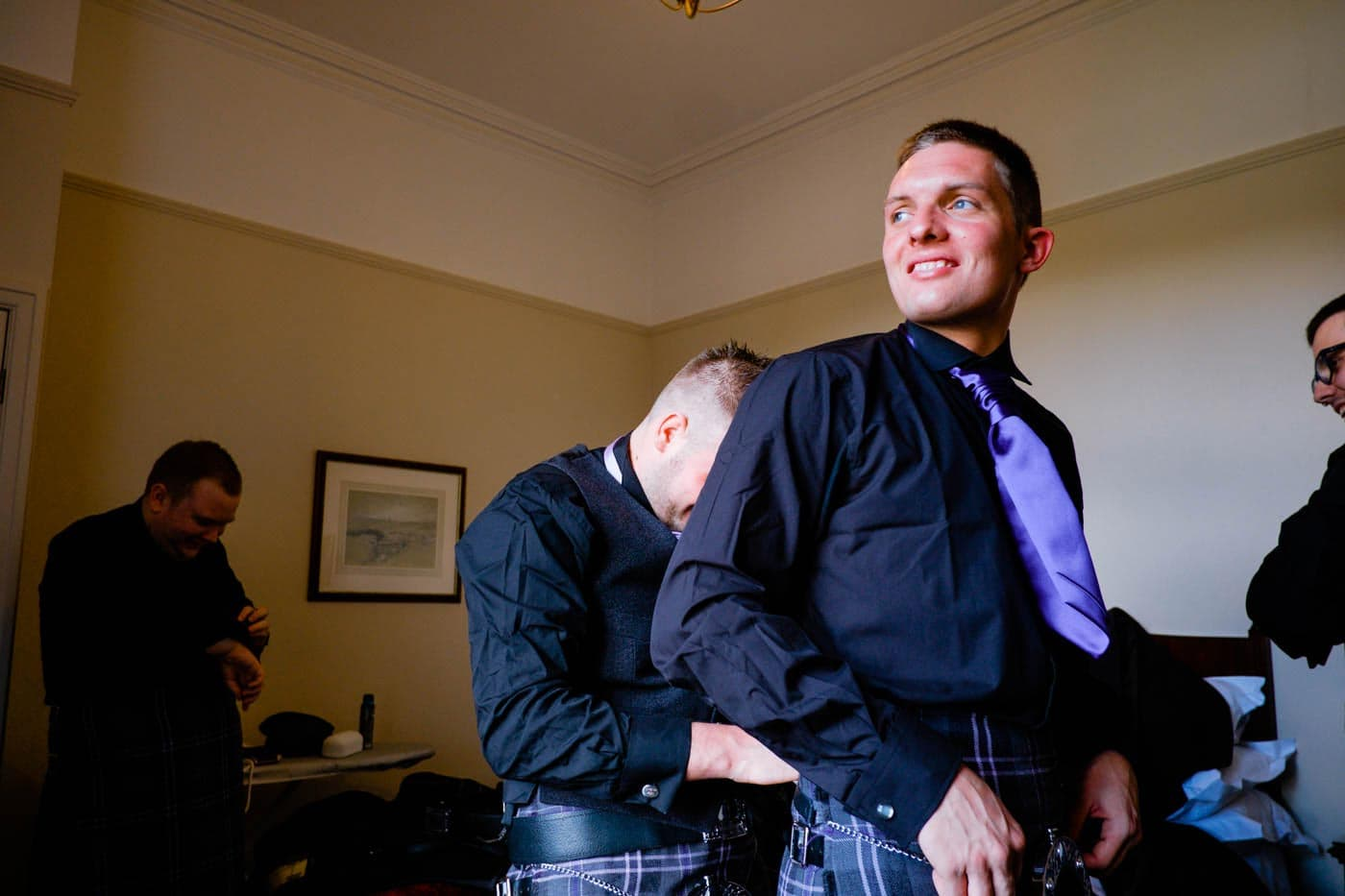 Groom being helped to get ready by Lake District wedding photographer Clive Blair Photography