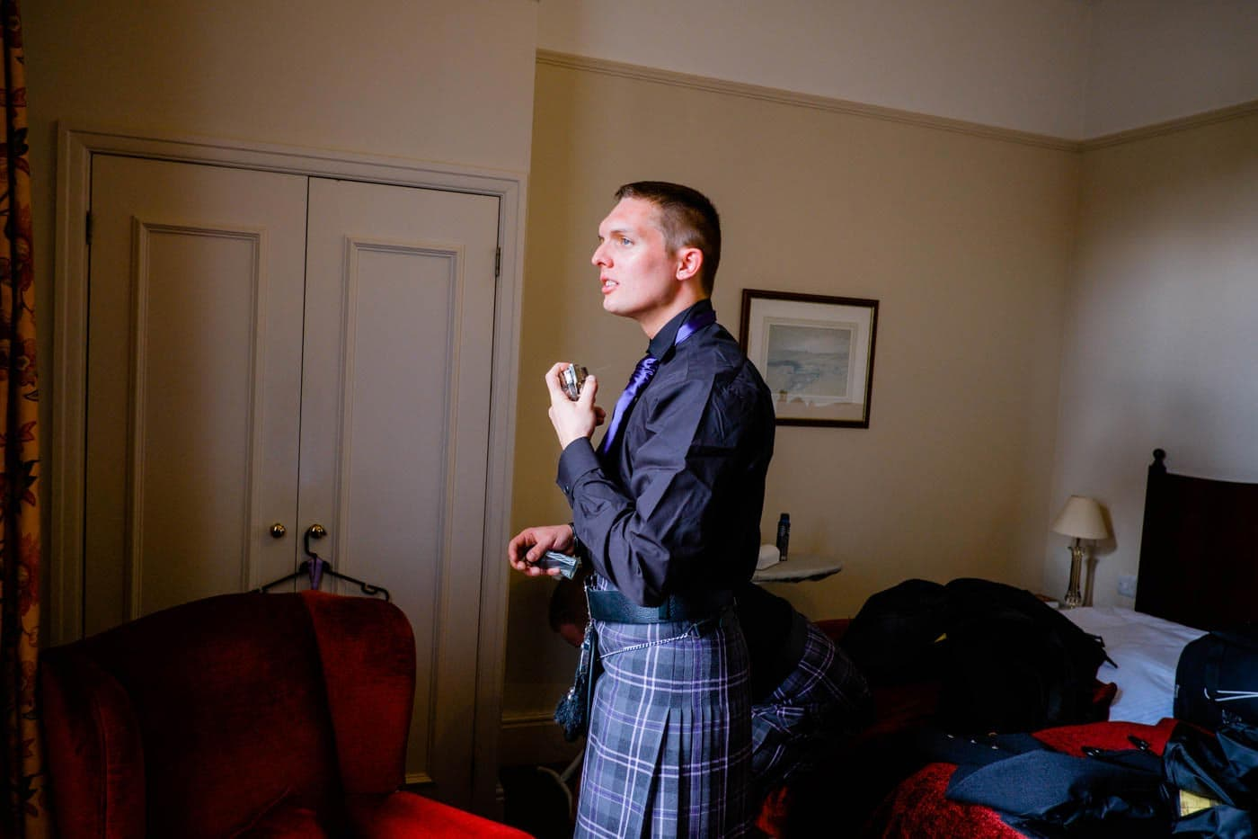 Scottish groom putting on his aftershave by Lake District wedding photographer Clive Blair Photography