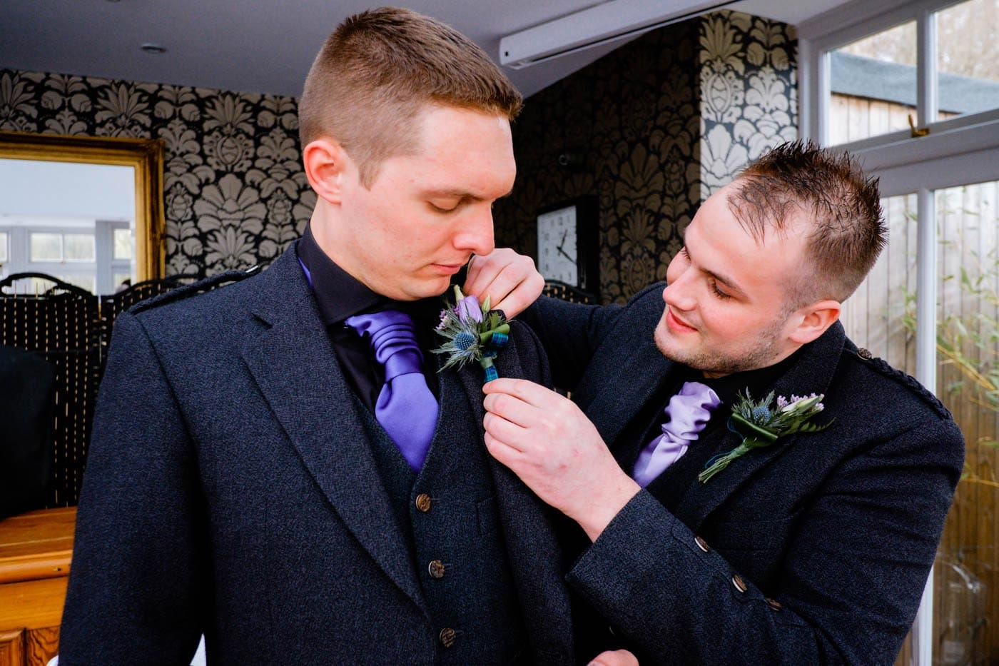 Scottish groom being helped with his button hole by Lake District wedding photographer Clive Blair Photography