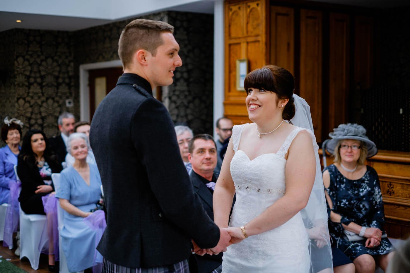 Happy Scottish bride and groom holding hands during their wedding ceremony at Broadoaks Country House