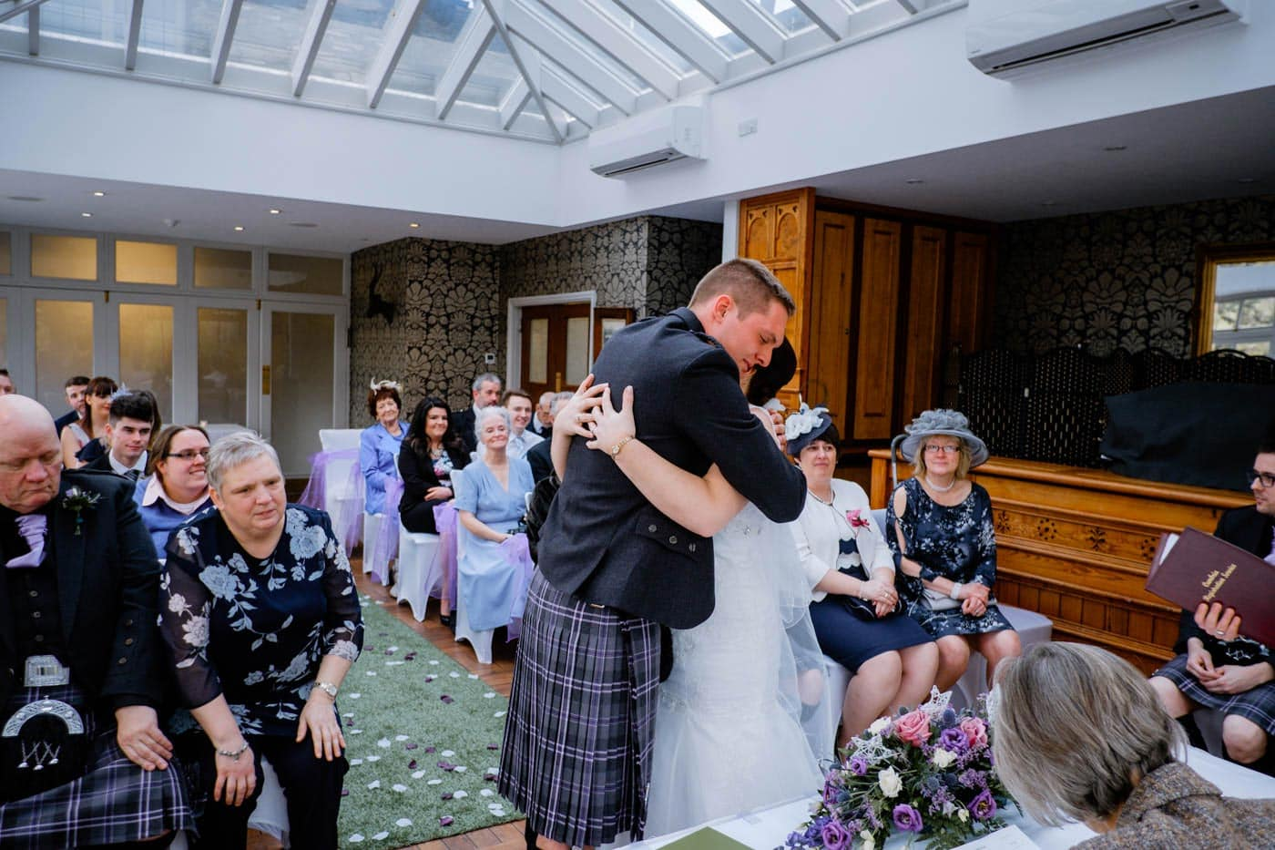 Scottish bride and groom hugging during their Lake District wedding ceremony at Broadoaks Country House