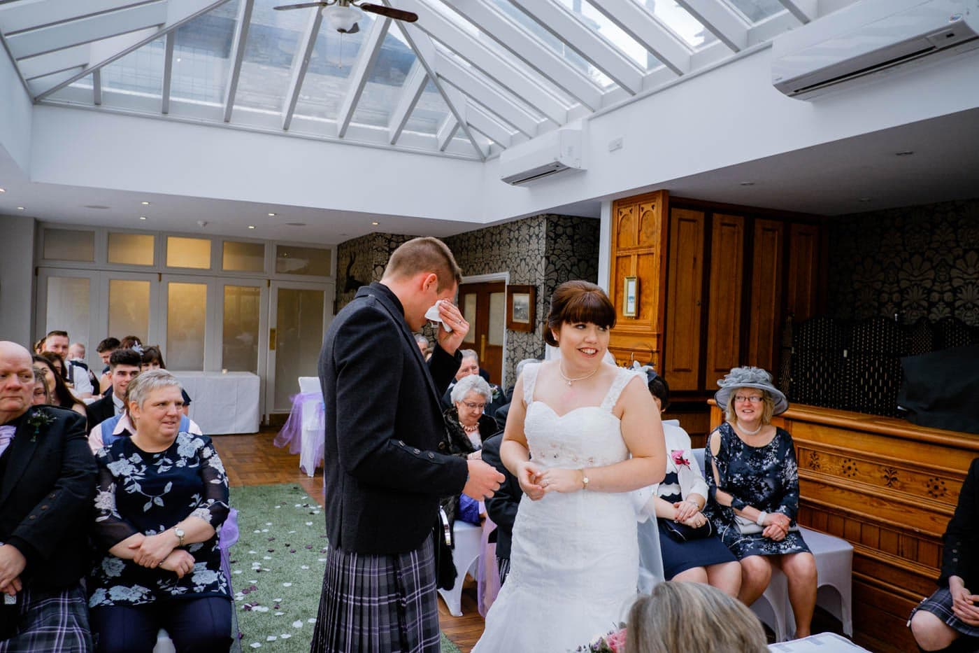 Scottish groom wiping away a tear during his wedding ceremony at Broadoaks Country House