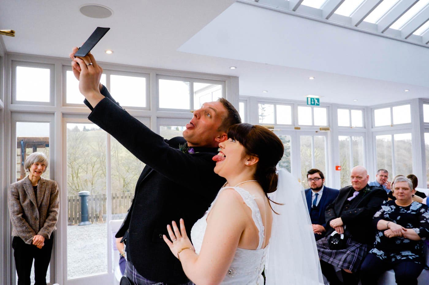 Bride and groom talking selfie after their wedding with their guests in the background