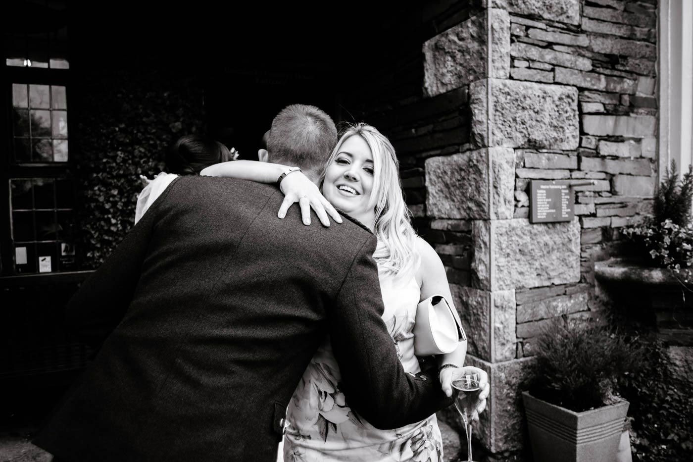 Woman guest hugging groom after wedding ceremony