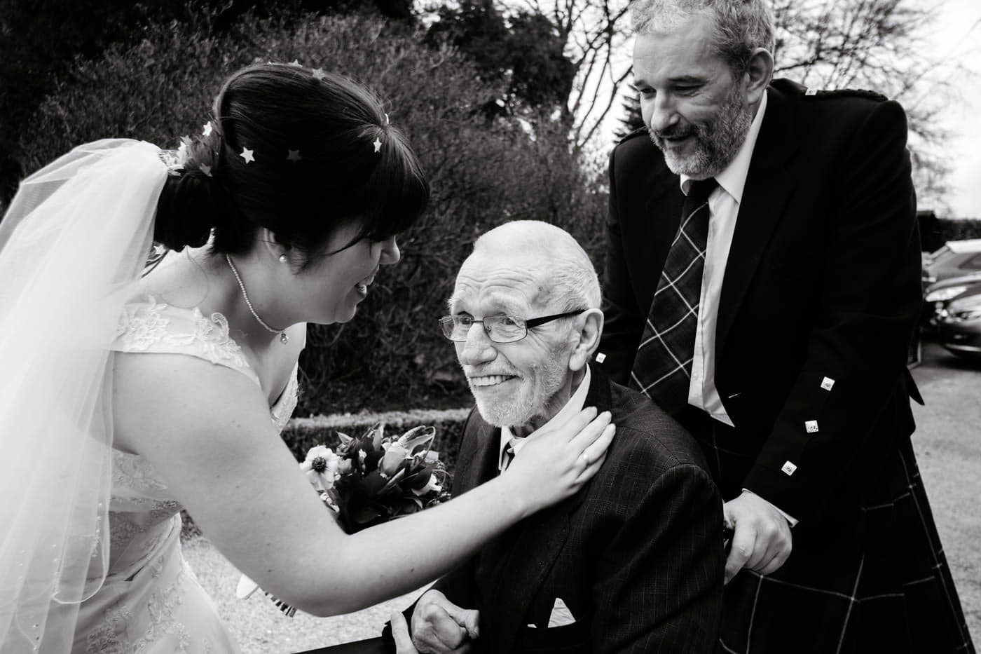 Bride greeting elderly guest after her wedding ceremony outside Broadoaks Country House