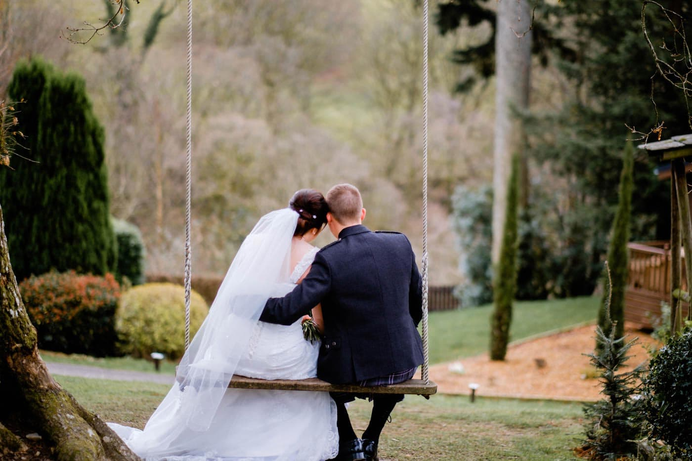 Bride and groom together on on swing at Broadoaks Country House by Lake District wedding photographer Clive Blair Photography