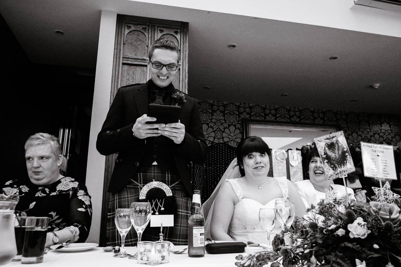 Bride pulling funny face during grom's speech by Lake District wedding photographer