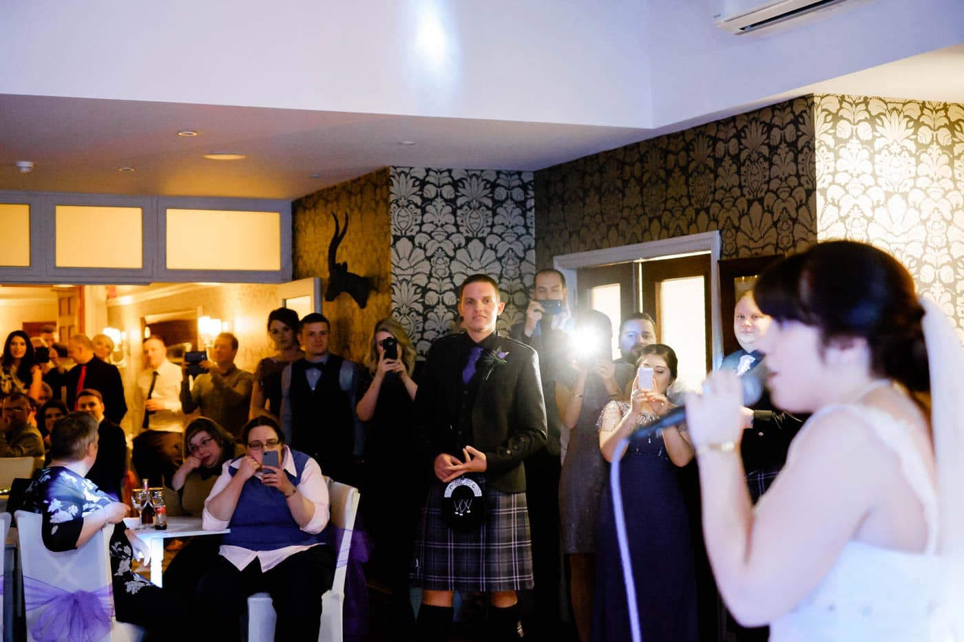 Scottish groom watching his bride sing a surprise song for him during the evening wedding reception