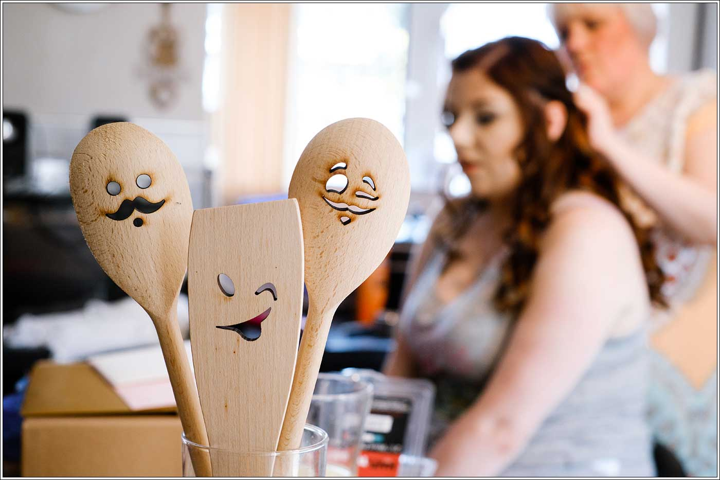 Bride getting ready in the morning with focus on wooden faces in sppons