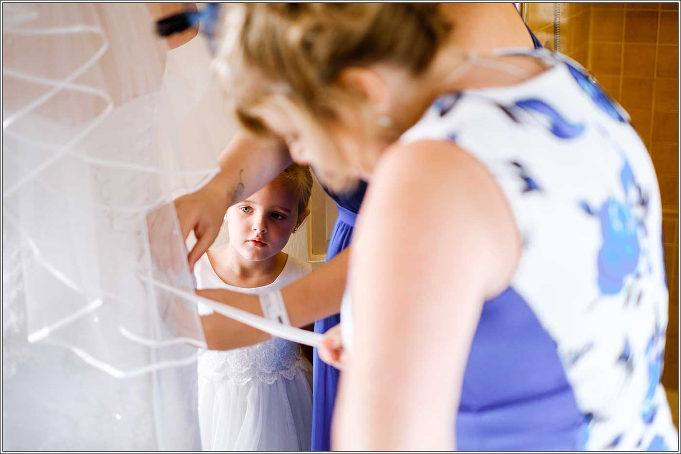 Maid peering at bride's dress being laced up