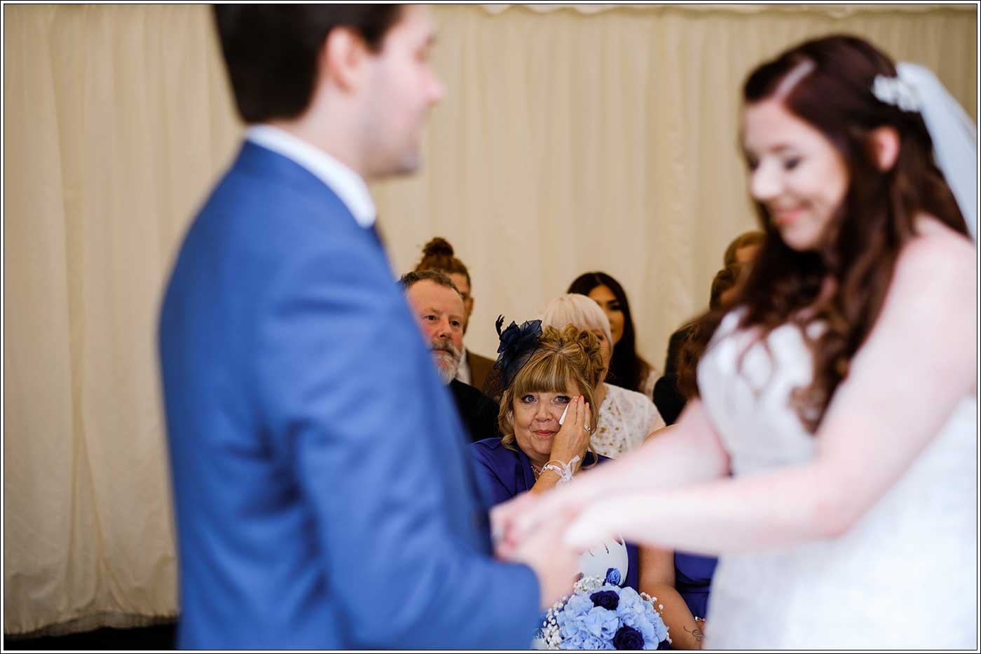 Mother of bride crying in background during her daughter's Park Hall Farm wedding