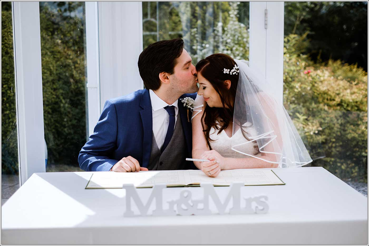 Groom kissing bride on her forehead