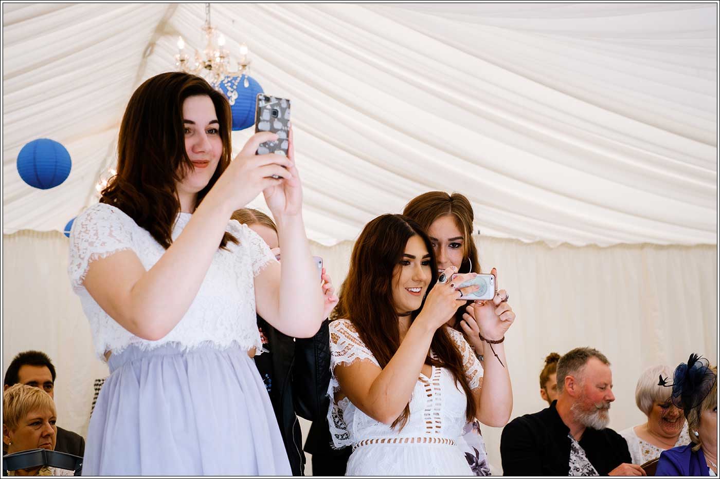 Guests taking photos of bride and groom