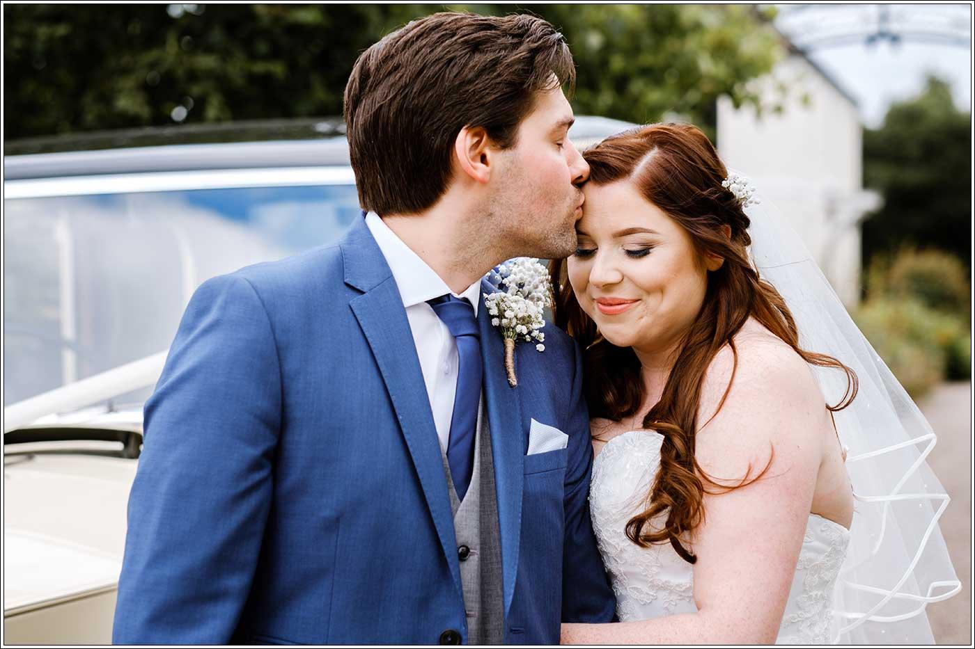 Groom kissing bride on her forehaed