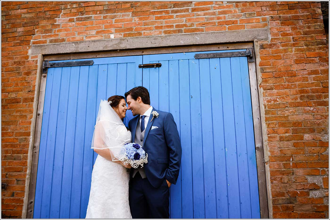 Bride and groom by blue door at Park Hall farm