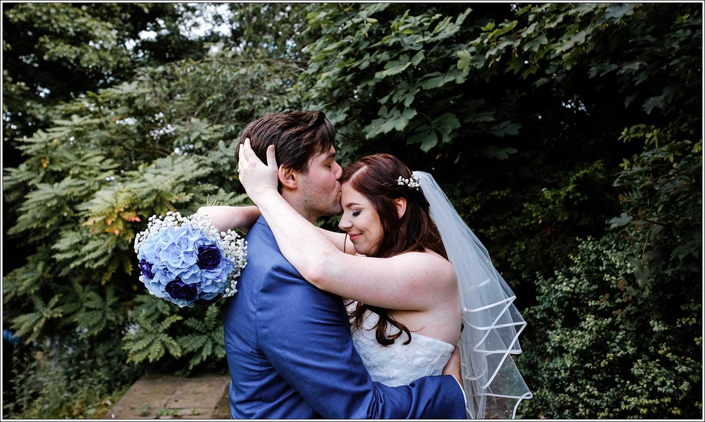 Bride hugging groom after their Park Hall Farm wedding