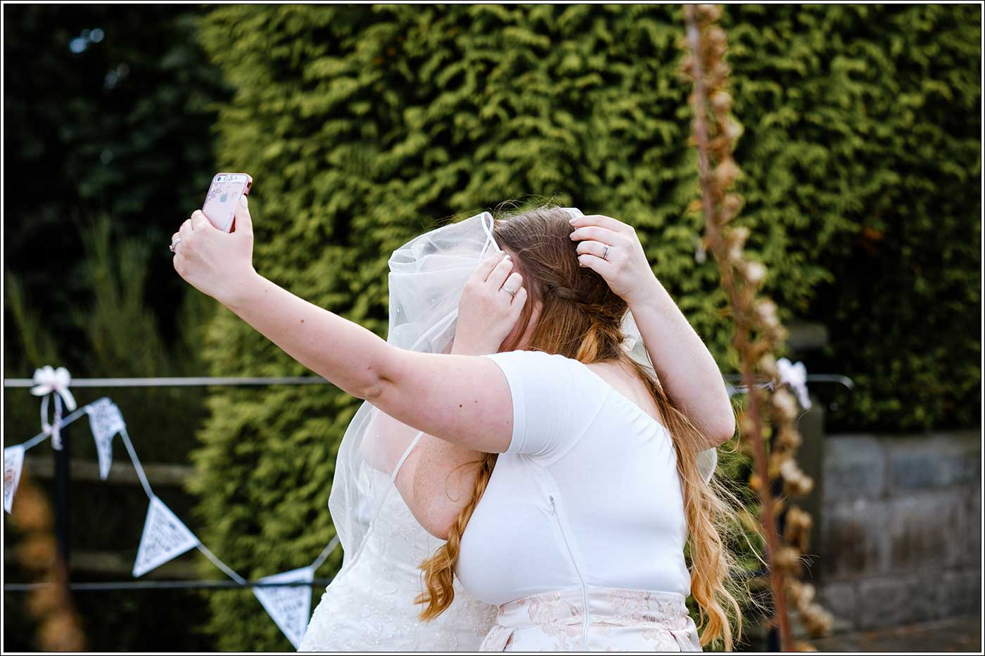 Bride and friend messing about taking selfie