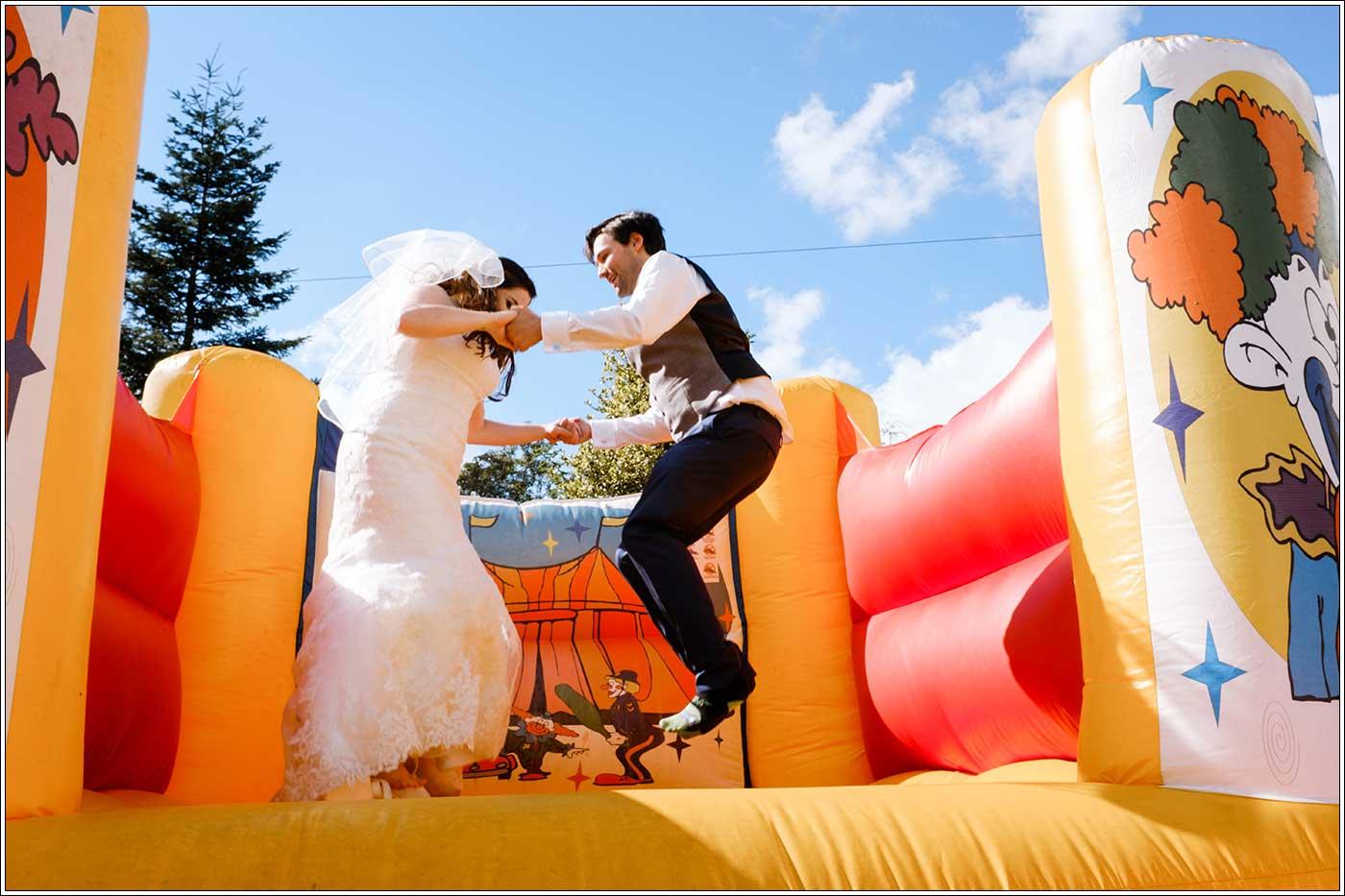 Groom and bride on bouncy castle at Park Hall Farm