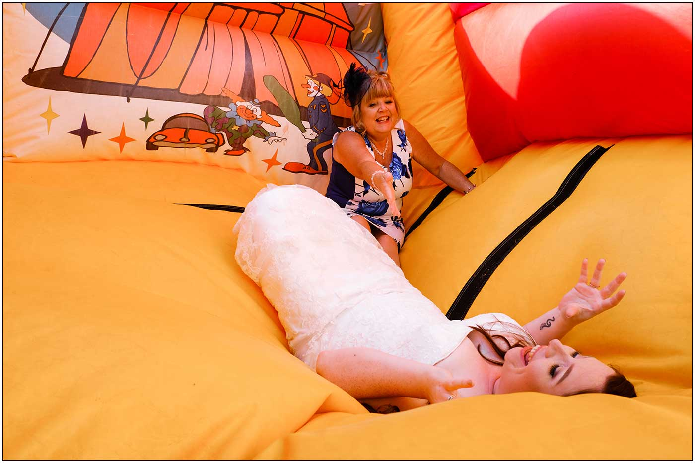 Bride and her mother on bouncy castle at Park Hall Farm