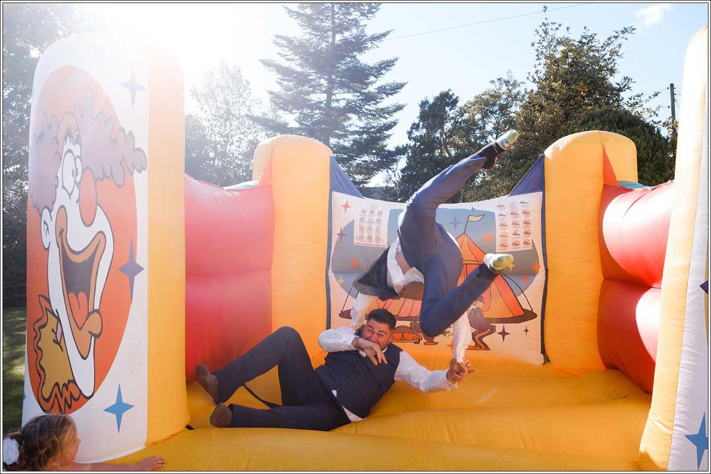 Groom and bestman on bouncy castle at Park Hall Farm