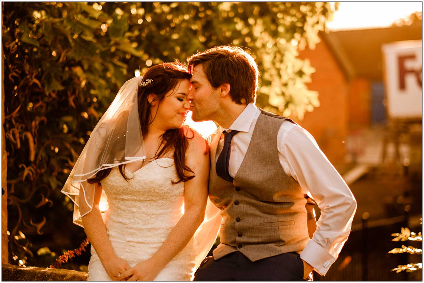 Groom kissing bride during the golden hour at Park Hall Farm