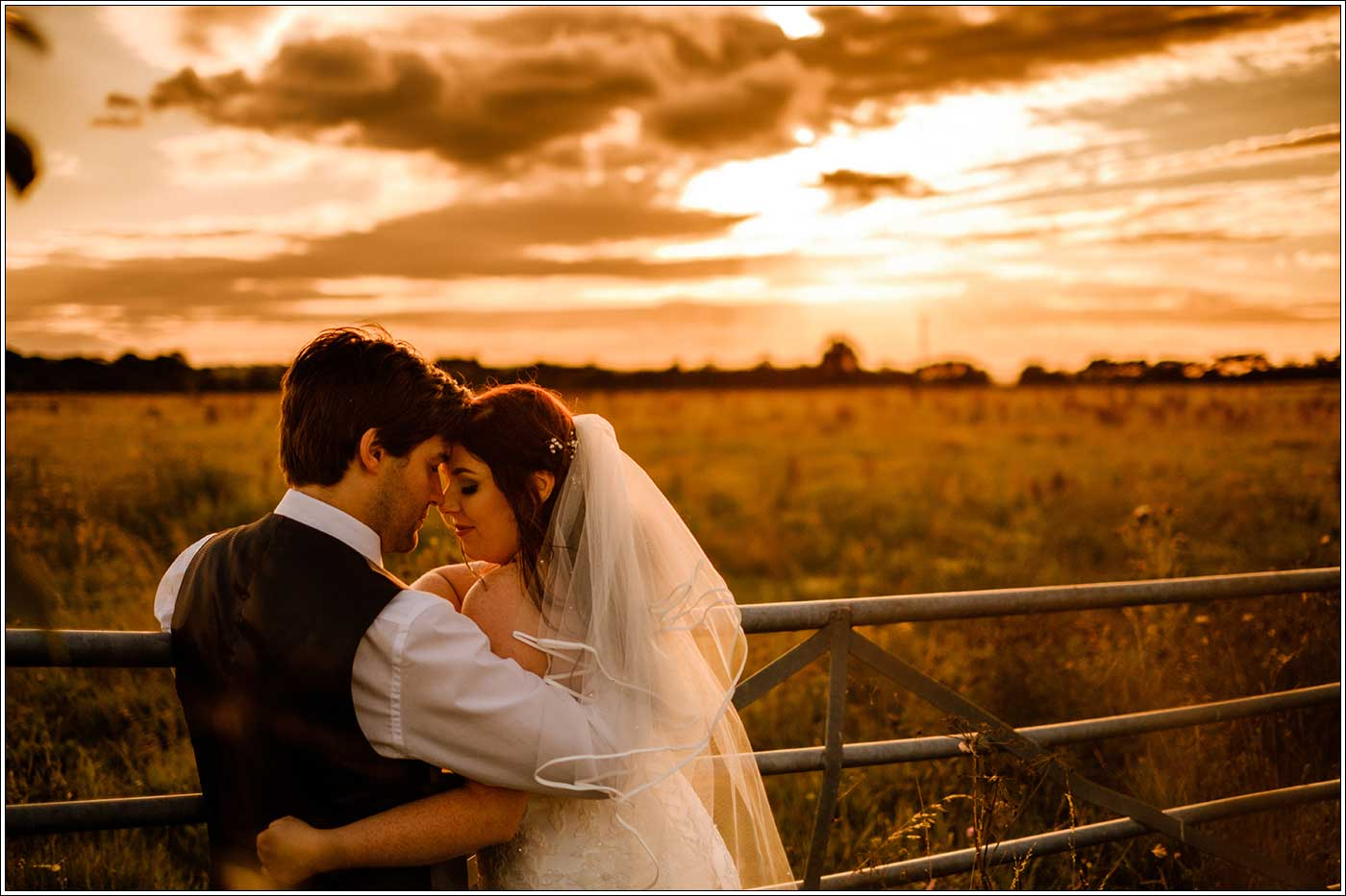 Bride and groom overlooking Park Hall Farm fields during the golden hour setting sun