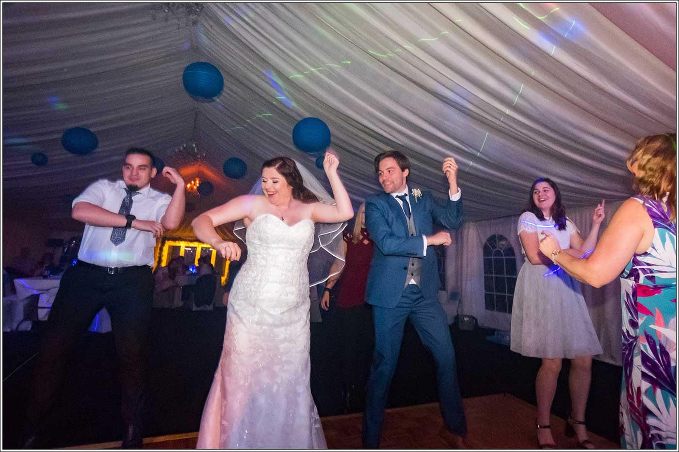 Bride, groom and guests on dancefloor