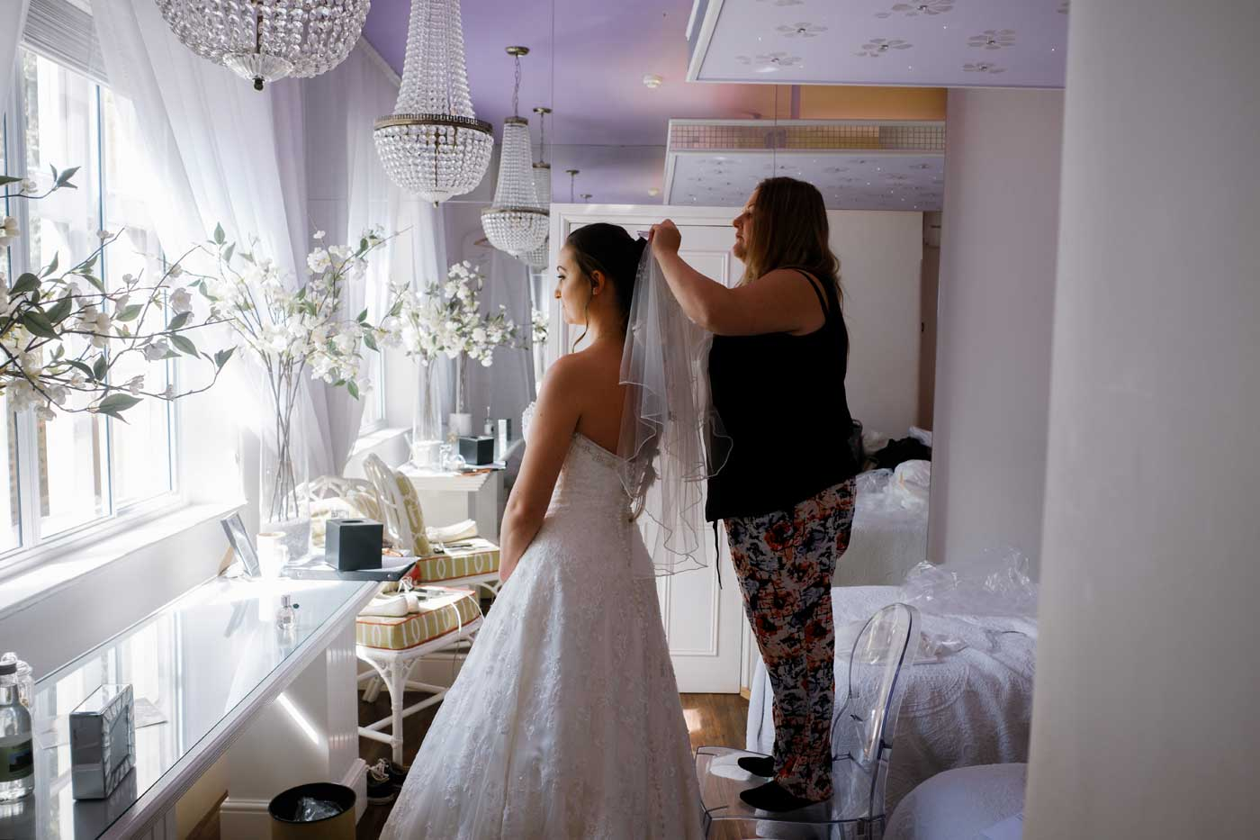 Bride having her veil put on before her Rowton Castle wedding ceremony