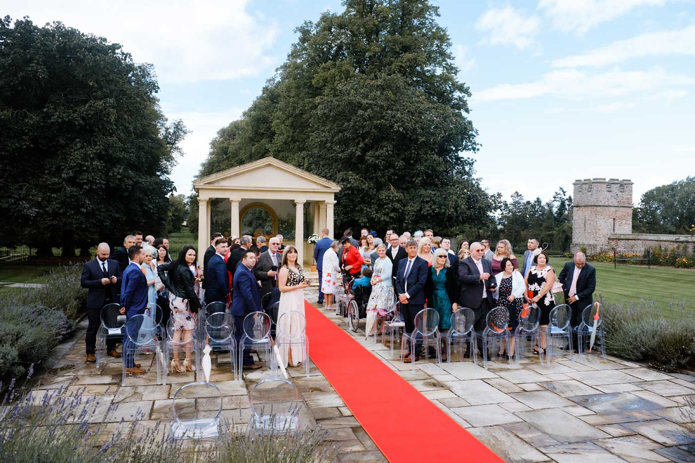 Guests standing as the bride and maids arrive for her outdoor ceremony at The Linden Belvedere at Rowton Castle