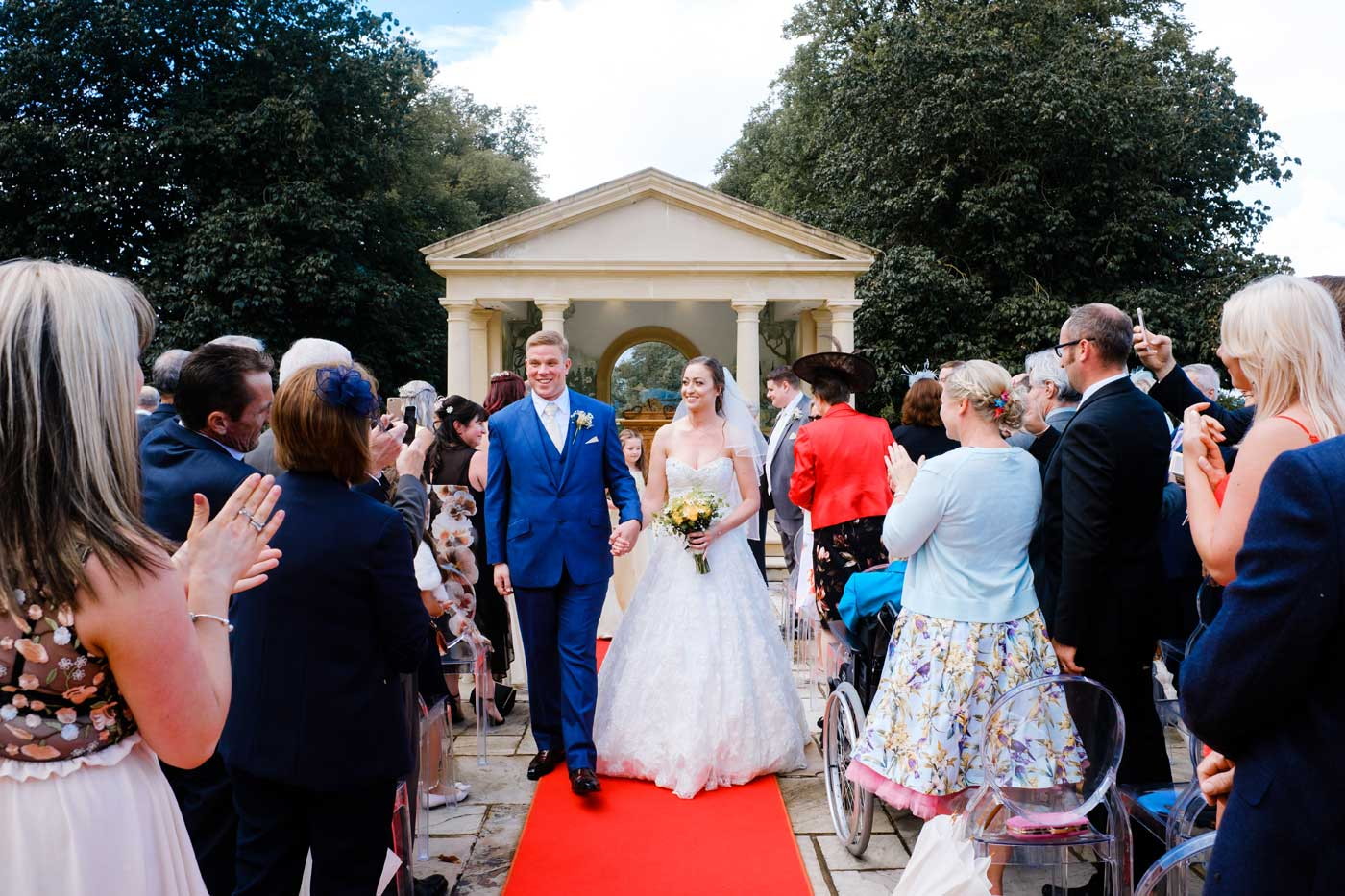 Groom and bride walking down the aisle after their Rowton Castle outdoo wedding ceremony