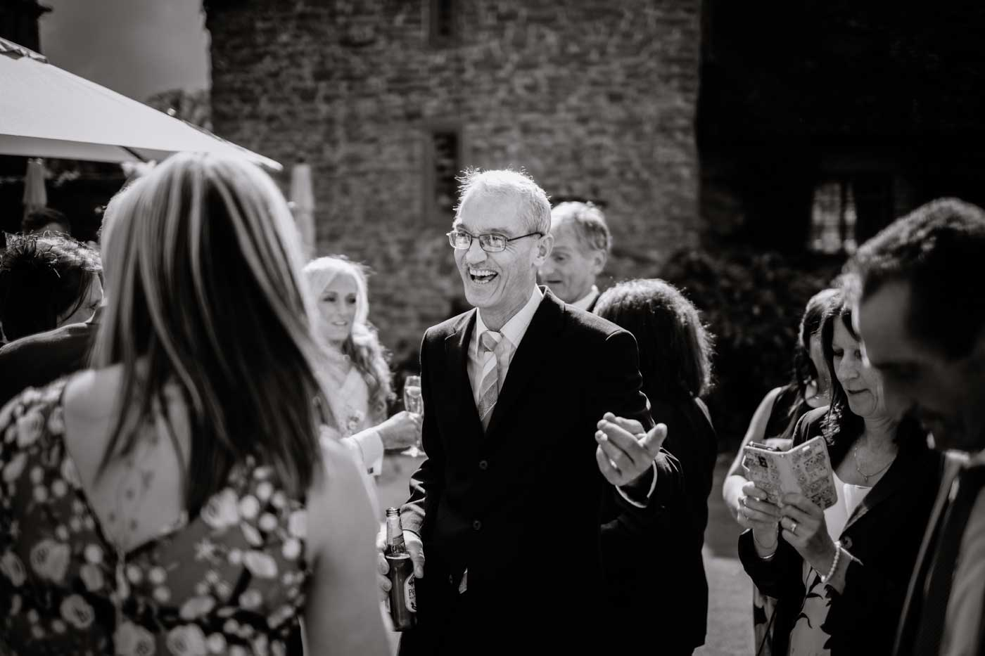 Happy man speaking to bride after her Rowton Castle wedding ceremony