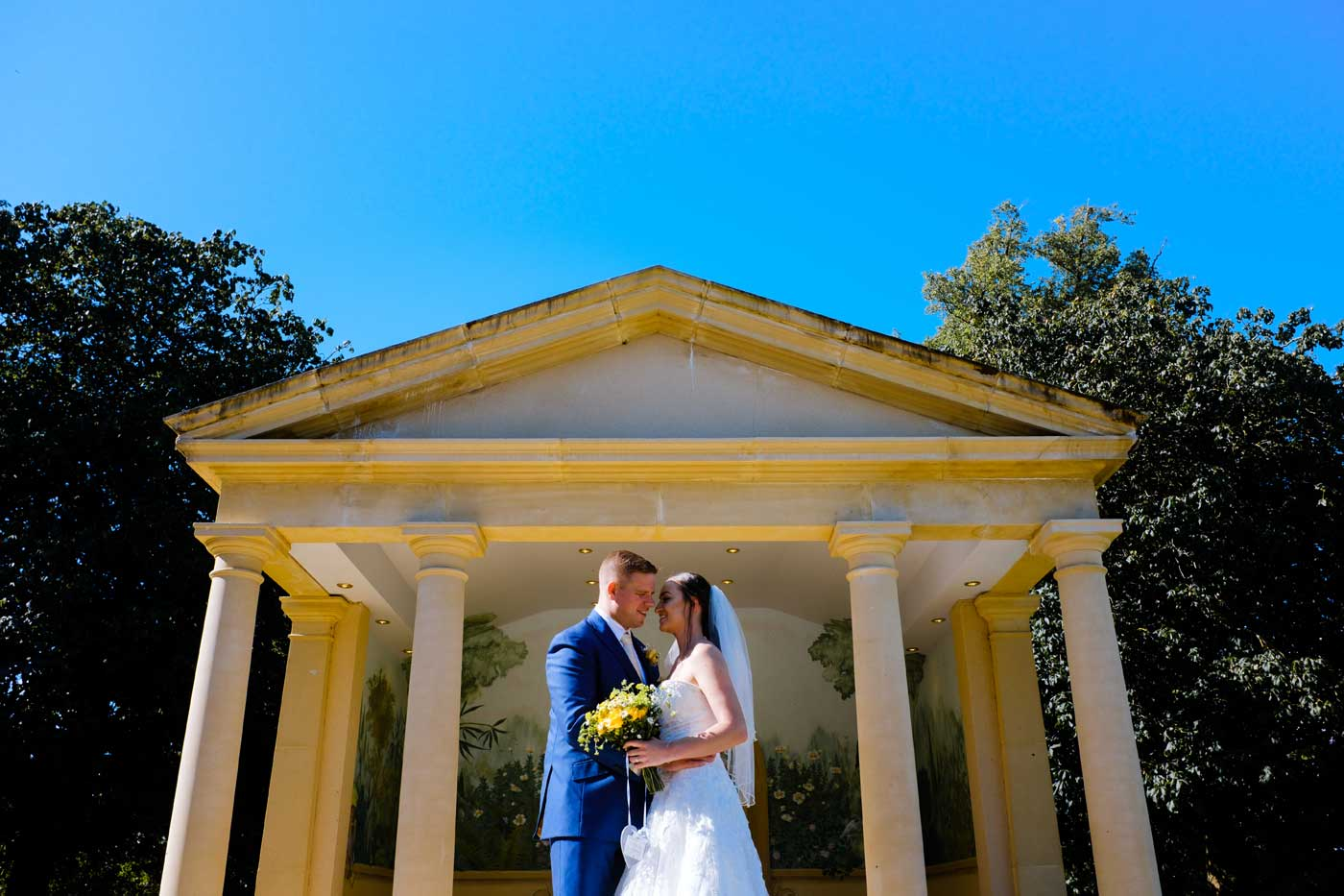 Groom and bride infront of the Linden Belvedere at Rowton Castle