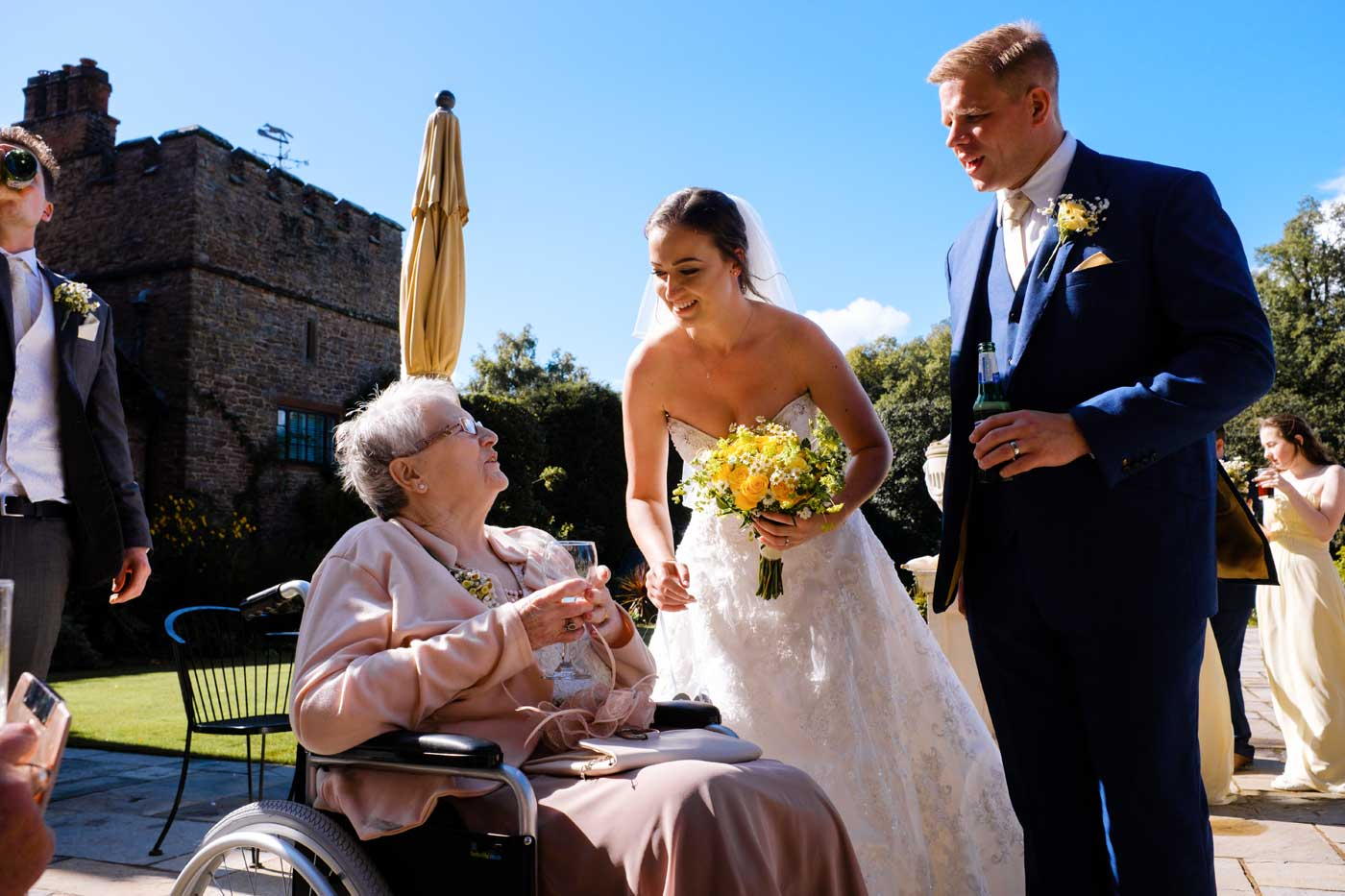 Groom and bride talking to woman in wheelchair at Rowton Castle