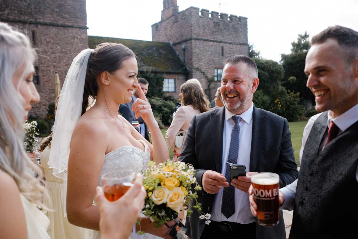 Bride laughing with men at Rowton Castle