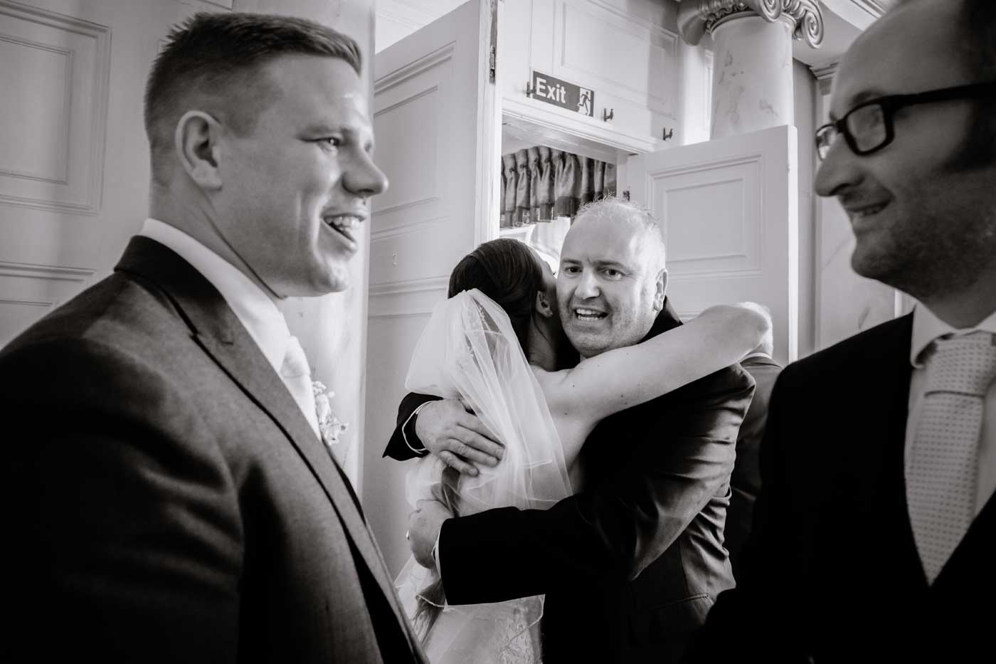 Man hugging bride by Rowton Castle wedding photographer Clive Blair Photographer