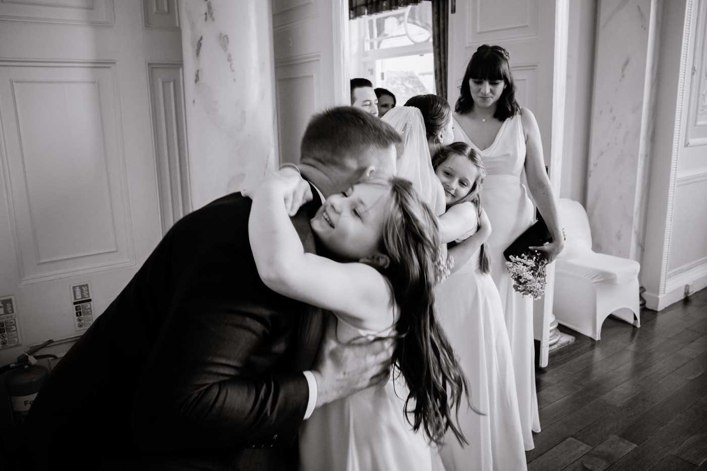 Maids hugging groom during receiving line at Rowton Castle