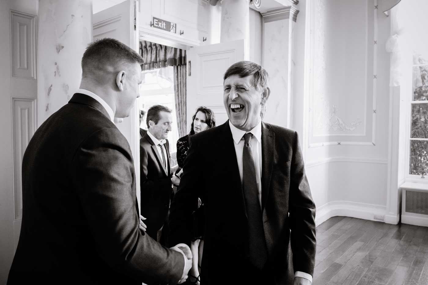Man laughing while shaking groom's hand during receiving line at Rowton Castle