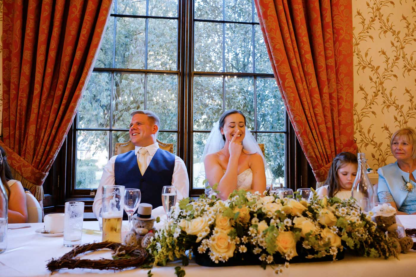 Embarressed bride and groom listening to bestman's speech at Rowton Castle