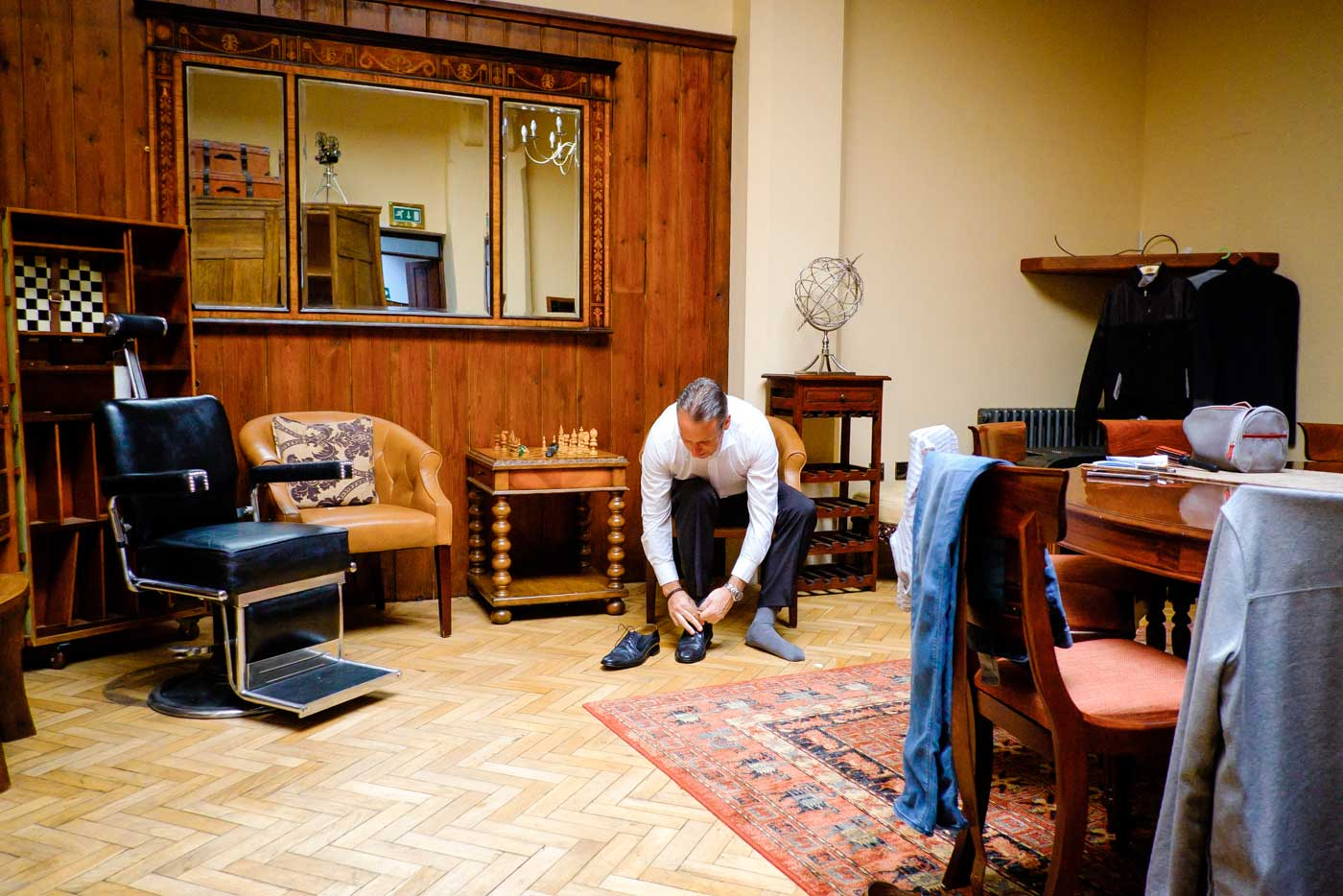 Groom putting on shoes in The Groom's room at Stanbrook Abbey by Stanbrook Abbey wedding photographer Clive Blair Photography